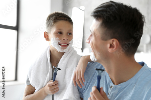 Fotografie, Obraz  Happy father and son with shaving foam on their faces in bathroom