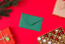 Top Above High Angle View Photo Of Green Envelope Surrounded With Gifts Presents Branch Of Fir Tree And Box Of Christmas Toys Isolated Vibrant Color Red Background