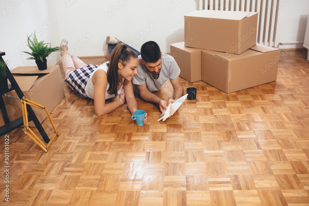 Fototapeta happy young family moving in their new home. choosing the color for interior walls