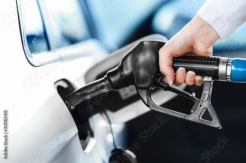 Valokuvatapetti Woman pumping petrol at gas station into vehicle