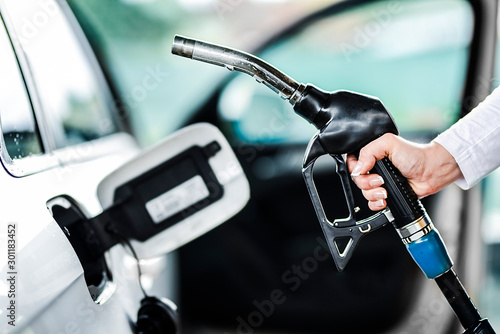 Woman pumping petrol at gas station into vehicle Fototapet