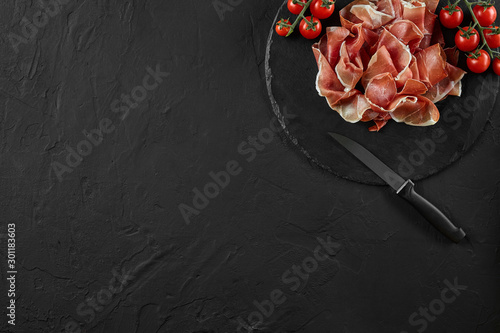Foto  Sliced jamon, cherry tomatoes and a knife on black stone slate board against a dark grey background