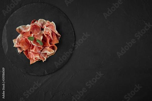 Cuadros en Lienzo Gourmet, manually sliced jamon with herbs on black stone slate board against a dark grey background
