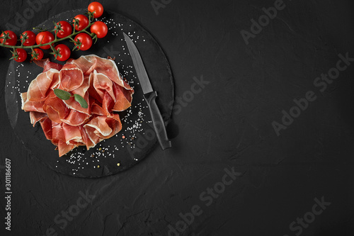 Sliced jamon, cherry tomatoes, herbs, spices and a knife on black stone slate board against a dark grey background Canvas