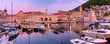 Leinwanddruck Bild - Panoramic view of Old Harbour with boats and Old Town of Dubrovnik at sunset, Croatia