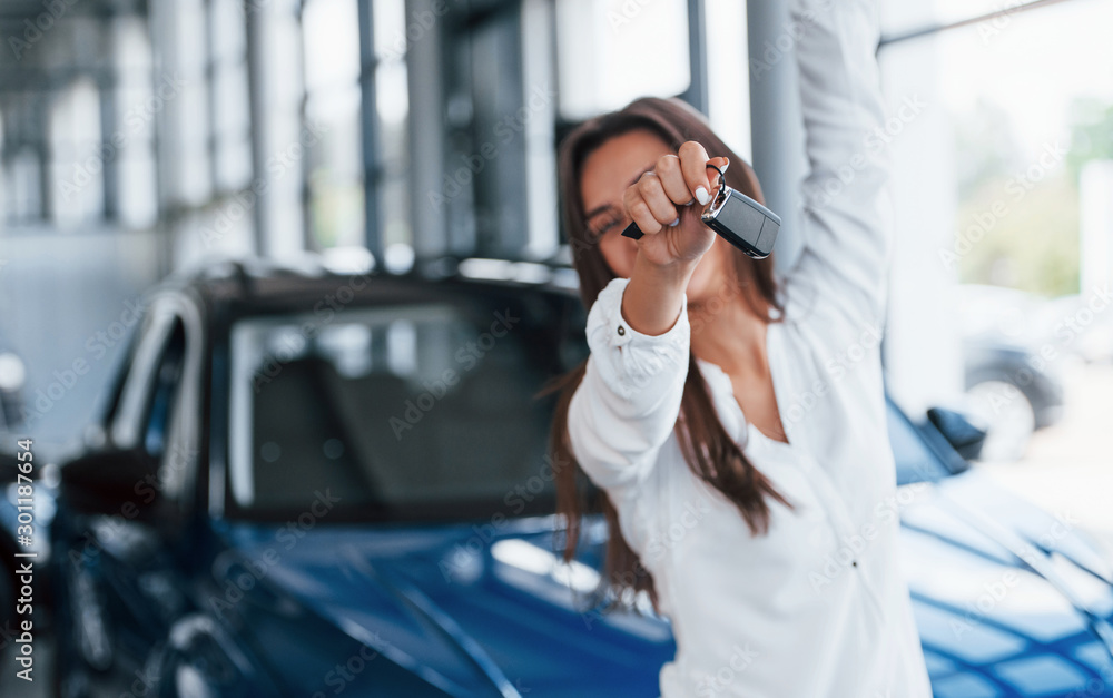 Fototapeta Excited with her new car. Holds keys in hand. Young woman in white official clothes stands in front of blue automobile indoors