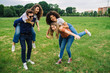 canvas print picture - Group of friends have fun at the park in summer - A man and three women joke among themselves - Two are on the shoulders of their companions