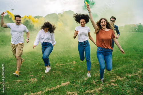 Group of five friends runs in a park with two smoke bombs at the park - Millennials have fun together in the summer at sunset - 301187870