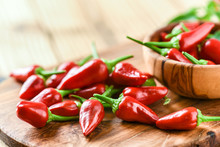 Red Hot Peppers In Old Wooden Bowl Side View. Chili Spicy Pepper On Table Copy Space.