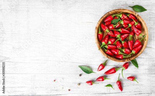 Photo  Red fresh chili peppers in wooden bowl on white old table