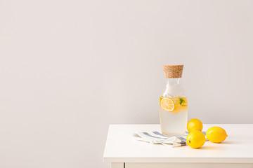 Bottle of cold lemonade on white table