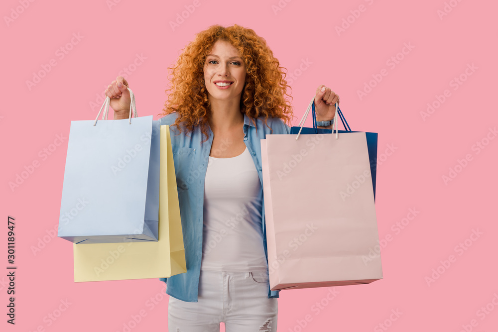 Fototapeta attractive girl holding shopping bags, Isolated On pink