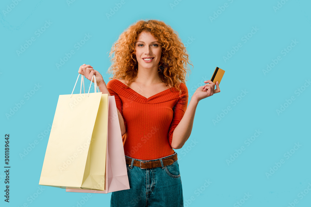 Fototapety, obrazy: smiling woman holding shopping bags and credit card, Isolated On blue