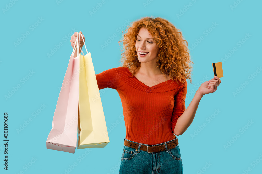 Fototapety, obrazy: beautiful girl holding shopping bags and credit card, Isolated On blue