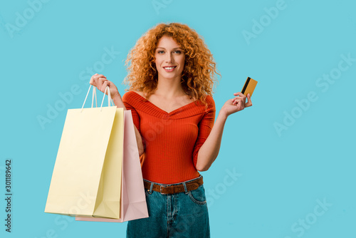 Keuken foto achterwand Dinosaurs smiling woman holding shopping bags and credit card, Isolated On blue