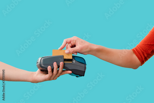 Fototapeta cropped view of woman paying with credit card on terminal, Isolated On blue