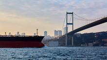 Turkey, Istanbul, Bosphorus Channel, Bosphorus Bridge, An Cargo Ship Under The Bridge.
