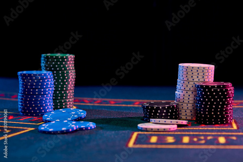 Colorful chips piles standing on blue cover of playing table Tableau sur Toile