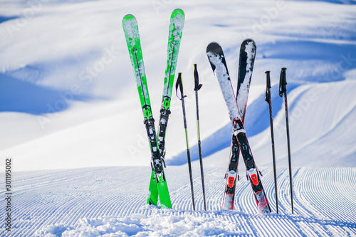 Skis in snow in winter season, mountains and ski items or equipments on the top Canvas Print