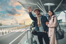 Young Man And Woman Stand Outside Airport And Wait For Taxi Cab. Guy Wave With Hand. After Vacation Or Travel. Georgian Woman Hold His Hand And Smile. Sunset Outside. Evening.