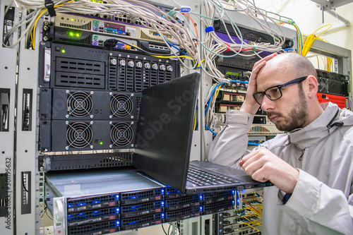 Fotografija Programmer with glasses made a mistake when working in the server room