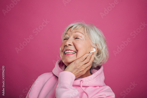 Foto  Portrait of old woman in pink hoody stand alone end enjoy listen to music