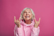 canvas print picture - Emotional, cheerful and happy old woman in modern pink hoody posing on camera alone. Look up and laughing. Lady with grey hair show rock signs. Isolated over pink background.