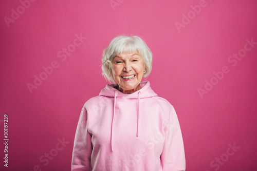 Obraz na plátne Happy cheerful positive old woman smiling wide and look straight on camera