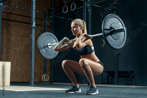 Fototapeta Indoors shot of muscular young woman doing squats with barbell in a gym. Female bodybuilder doing workout Confident young blonde woman doing crossfit workout in gym Powerful attractive woman obraz