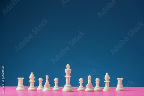 Fotobehang Europa White chess figures positioned on pink board with king piece as the lead