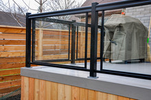 A Newly Constructed Backyard Deck Uses Wood Composite, Cedar Skirting And Glass And Metal Railings, While Asian Inspired Horizontal Fencing Helps Complete The Contemporary Feel.