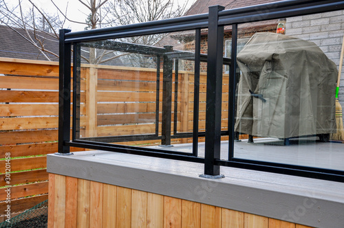 Obraz A newly constructed backyard deck uses wood composite, cedar skirting and glass and metal railings, while Asian inspired horizontal fencing helps complete the contemporary feel. - fototapety do salonu
