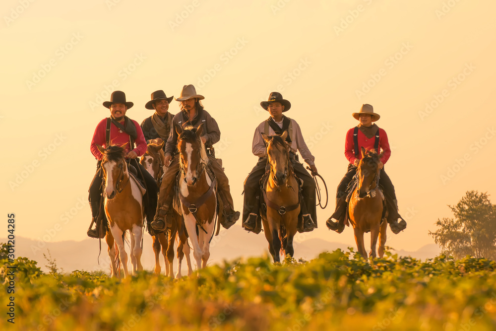 Fototapety, obrazy: Group of Cowboy riding horse.Silhouette Cowboy on horseback.Cowboy  riding horse at sunset or sunrise time.