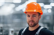 Portrait of male industrial worker indoors in factory. Young technician with orange hard hat