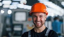 Smiling And Happy Employee. Portrait Of Industrial Worker Indoors In Factory. Young Technician With Orange Hard Hat