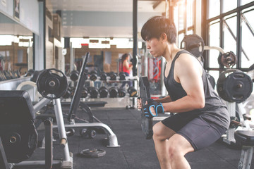 The young man who beginner training with free weigth in gym. Fitness concept.Fitness muscular body.