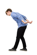 Bent Down Teenage Guy Keeps Hands Back As Carrying An Heavy Invisible Object On His Shoulders Isolated On White Background. Overloaded Boy Tired Of Daily Routine, Difficult Task And Burden Concept.
