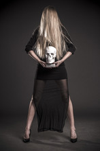 Mystical Portrait Of A Blonde Girl A Skull. Dark Background. Halloween