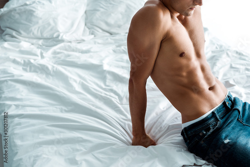 Fotografía cropped view of shirtless man sitting on bed at home