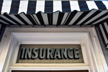 A Vintage Sign In Silver Type On A Transom Window Reads INSURANCE, While A Bold Black And White Awning Flutters Overhead.