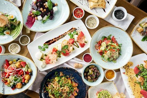 Fototapeta Variety of dishes on the table. Various snacks and antipasti on the table. Restaurant menu. Italian cuisine obraz