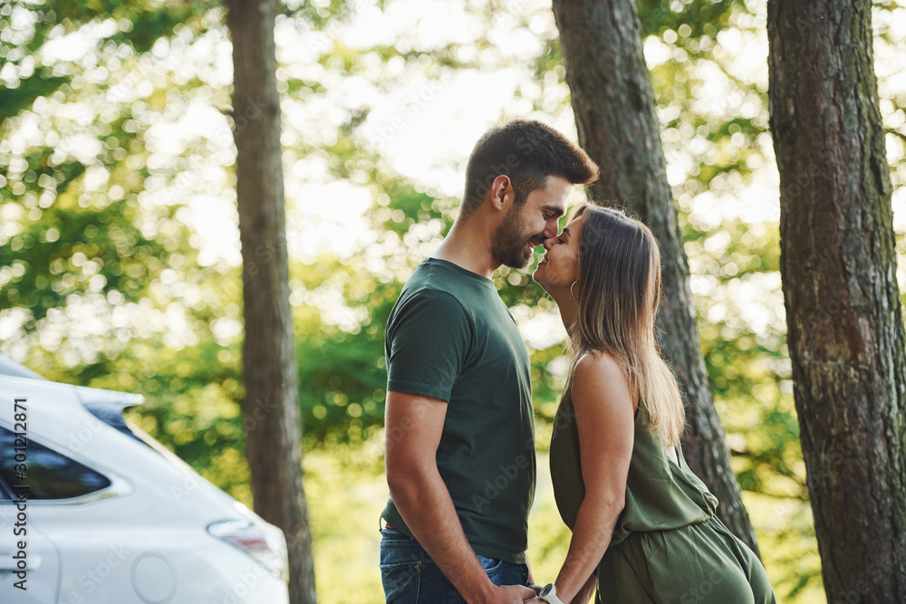Fototapeta Near white colored car. Beautiful young couple have a good time in the forest at daytime