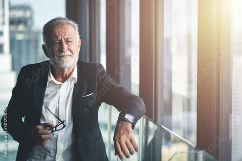 Pinturas sobre lienzo  Portrait of sophisticated senior CEO businessman leaning on the glass railing indoors