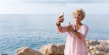 Mature Woman Taking Selfie On ...