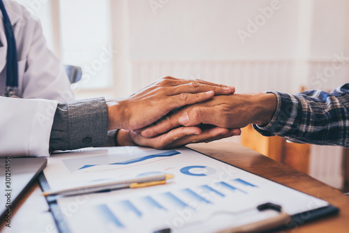 Carta da parati Young doctor hands holding patient hand for encouragement after talking about sexually transmitted diseases and venereal cancer detected
