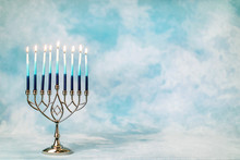 A Silver Menorah For The Jewish Holiday Hanukkah With Burning Glowing Eight Candles On Fire Lit Up On A Blue Background With Copy Space