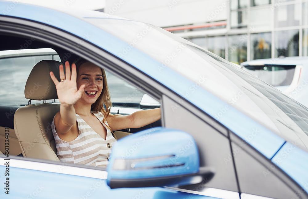 Fototapety, obrazy: Bye, gesture. Female driver inside of modern automobile. Testing brand new car