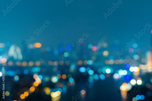 Obraz Bokeh background of skyscraper buildings in downtown. Urban city with lights, Blurry photo at night time.  illuminated Cityscape - fototapety do salonu