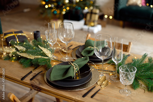 Table served for Christmas dinner in living room, close-up view, table setting, Christmas decoration. - 301236261