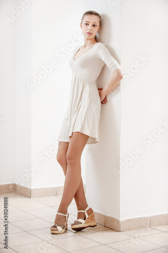Cuadros en Lienzo young beautiful woman in white dress leaning on the wall